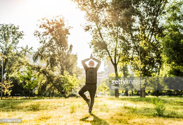 senior man doing yoga outdoors in city park. - holy city park stock pictures, royalty-free photos & images
