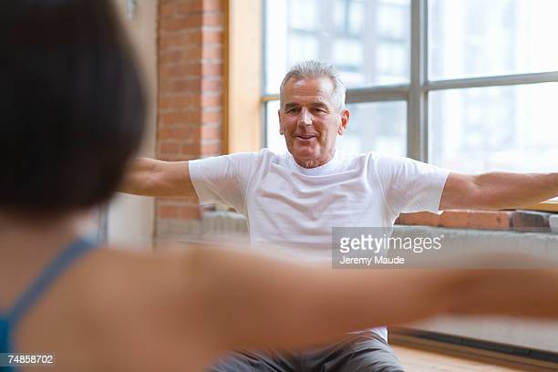 Senior man doing yoga with instructor