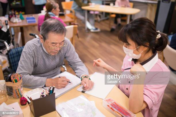 Senior man drawing picture with female nurse