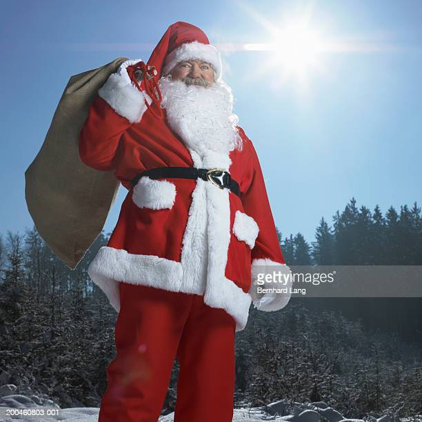 Senior man dressed as Father Christmas in forest, holding sack