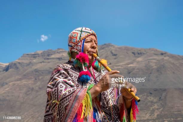 seniorenmensand, der traditionelle peruanische kleidung und spielflöte kleidet - tradition stock-fotos und bilder
