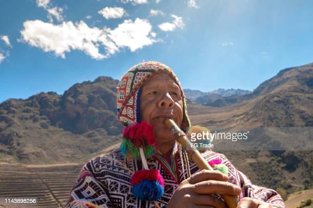 hombre mayor vestir ropa tradicional peruana y tocar la flauta - vestido tradicional fotografías e imágenes de stock