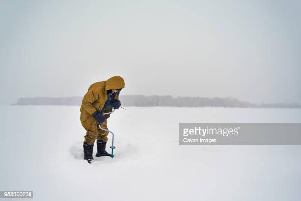 Senior man drilling in frozen lake against clear sky
