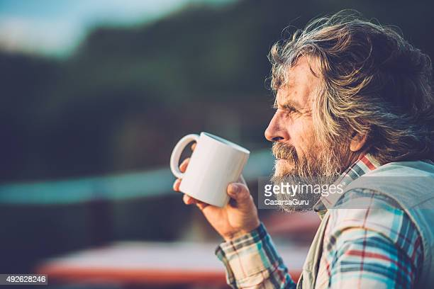 senior man drinking a coffee or a tea outdoors, close-up - extreme terrain stock pictures, royalty-free photos & images