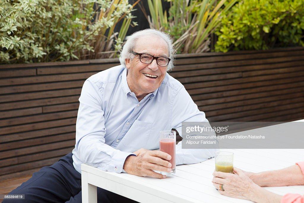Senior man drinking glass of juice : Stock Photo