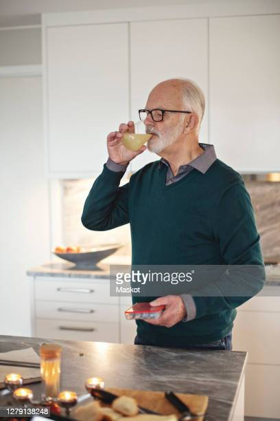 senior man drinking juice while standing by kitchen island at home - juice drink stock pictures, royalty-free photos & images