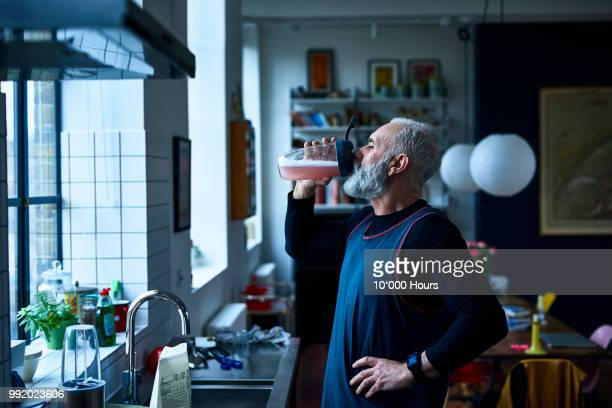 senior man drinking nutritional sports drink by kitchen sink - squash sport stock pictures, royalty-free photos & images