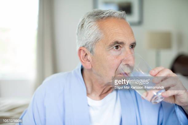 senior man drinking water from glass in bedroom - thirsty stock pictures, royalty-free photos & images