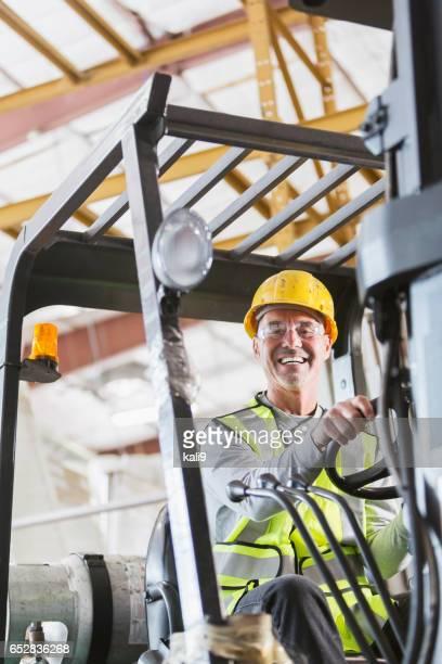 Senior man driving a forklift