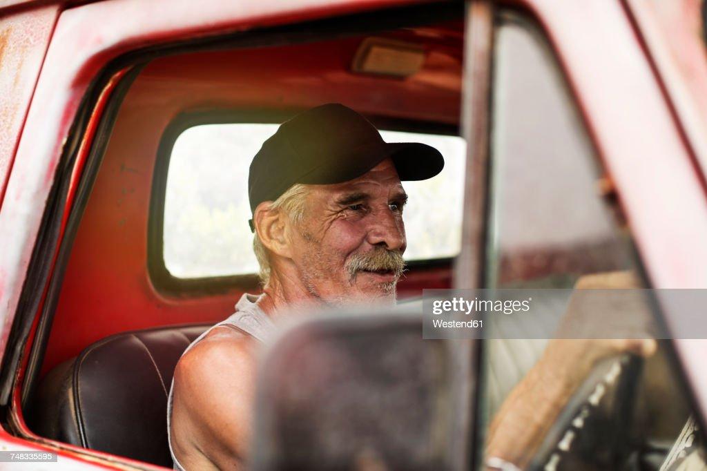 Senior man driving an old pick up : Stock Photo
