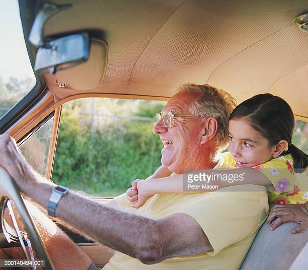 Senior man driving car embraced by girl (6-8) in back, laughing