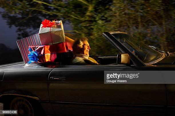 Senior man driving car full of presents.