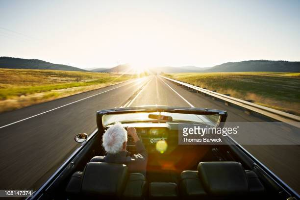 Senior man driving convertible car at sunrise