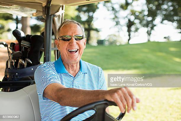 Senior man driving golf cart