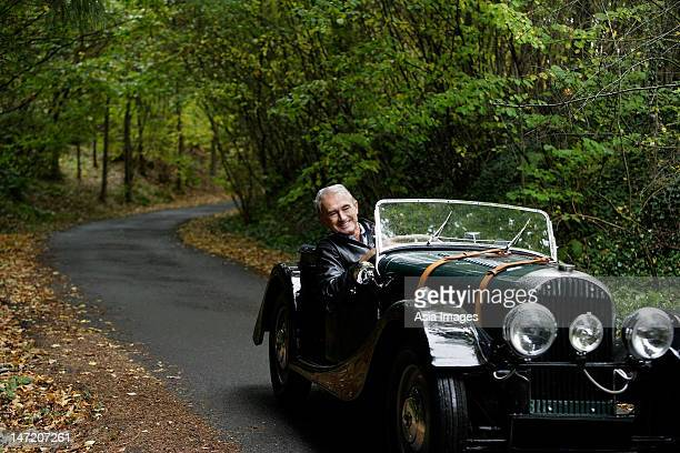 senior man driving in antique car