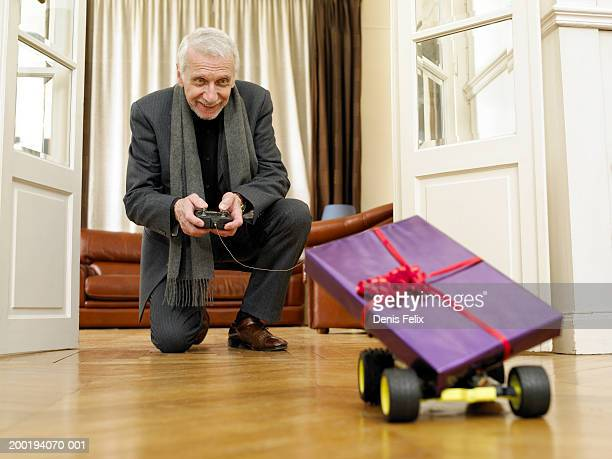 senior man driving remote control car carrying gift-wrapped present - remote controlled stock photos and pictures