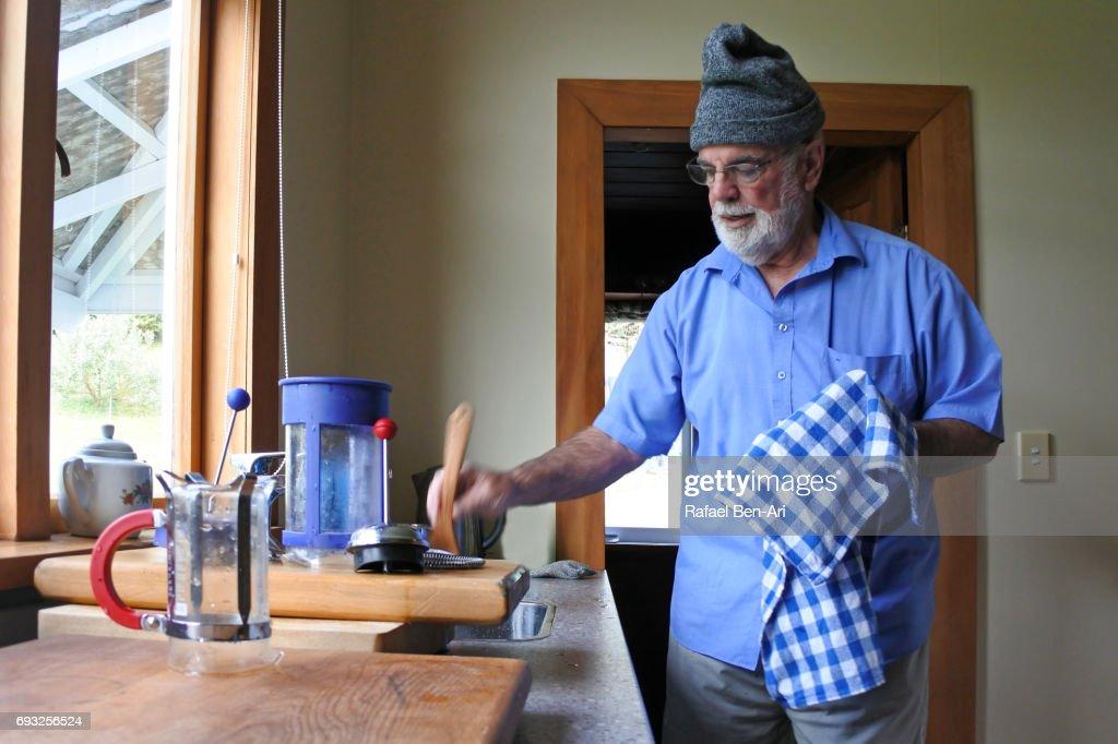 Senior man drying dishes : Stock Photo