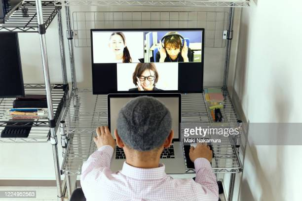 senior man during a video conference at home. - テレビ会議 ストックフォトと画像