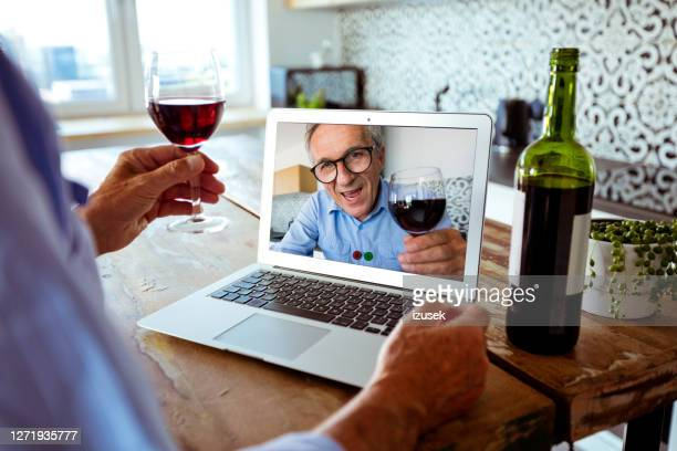 senior man during video call - celebratory toast stock pictures, royalty-free photos & images