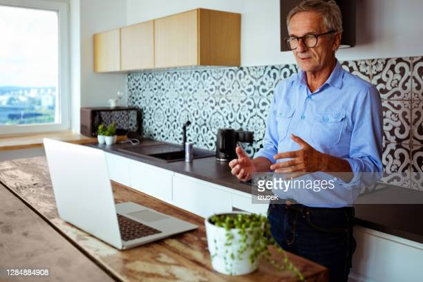 senior man during video conference at home - izusek stock pictures, royalty-free photos & images