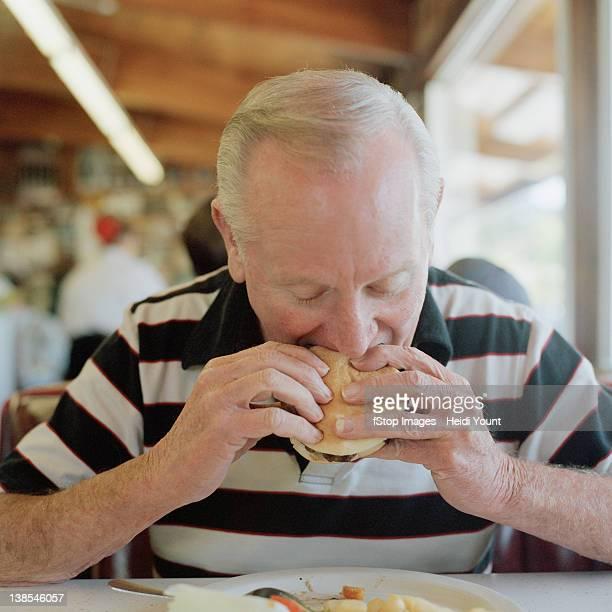 A senior man eating a hamburger