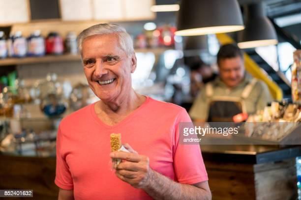 Senior hombre comiendo una barra de proteína en el gimnasio