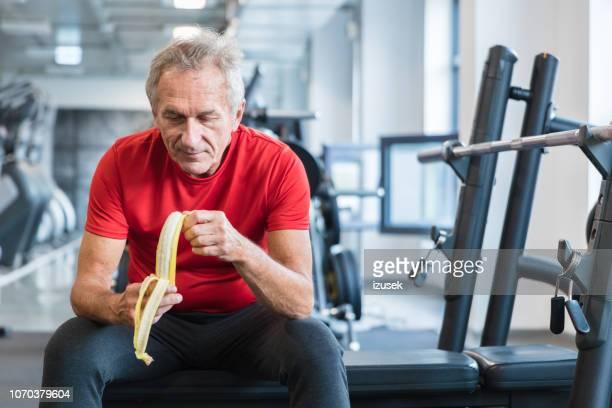 senior man eating banana during rehabilitation in gym - drug rehab stock pictures, royalty-free photos & images
