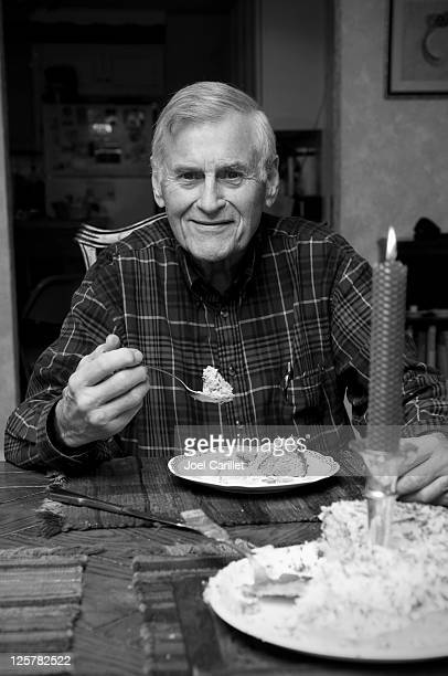 Senior man eating birthday cake at kitchen table