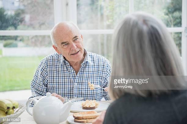 Senior man eating breakfast, listening to his wife