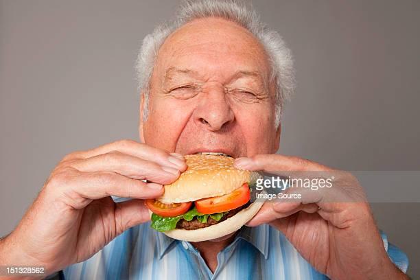 Senior man eating burger