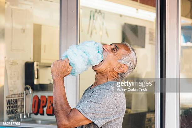 Senior man eating cotton candy, Long Beach, California, USA