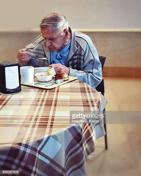 Senior Man Eating Food While Sitting At Table In Hospital