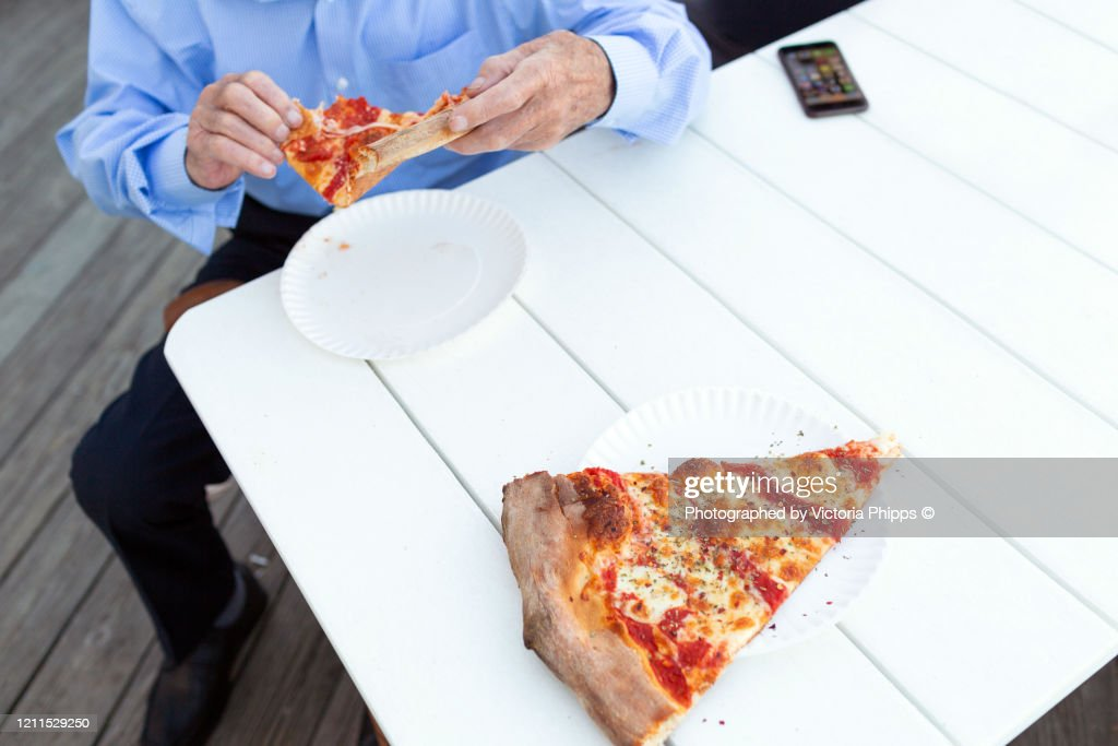 Senior man eating pizza outdoors : Stock Photo