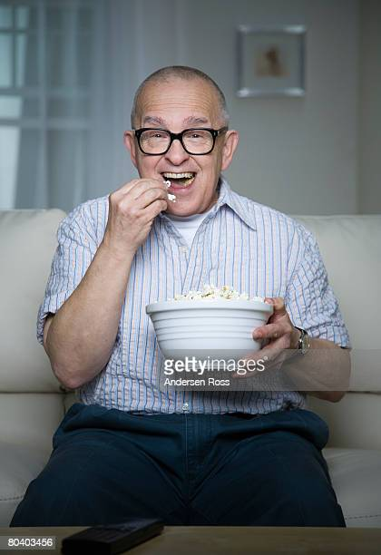 Senior man eating popcorn on couch