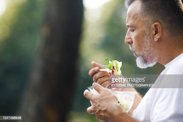 senior man eating salad - green salad stock pictures, royalty-free photos & images