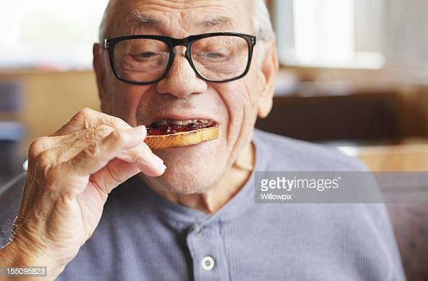 Senior Man Eating Toast and Jelly Jam