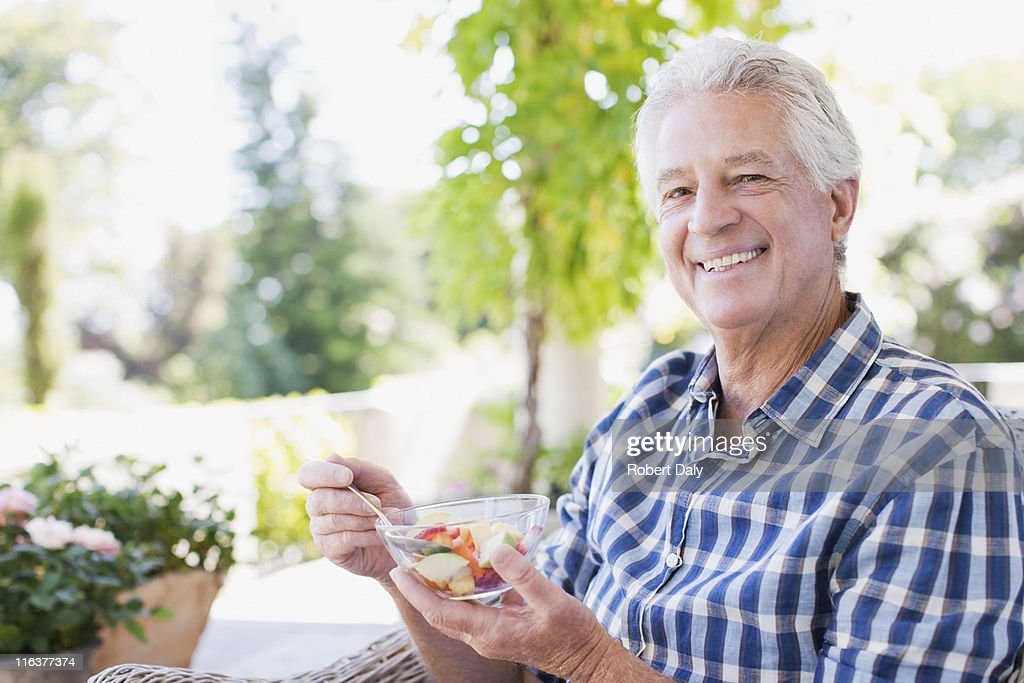 Senior man eating vegetables on patio : Stock Photo