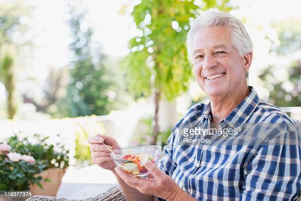Senior man essen Gemüse auf dem patio