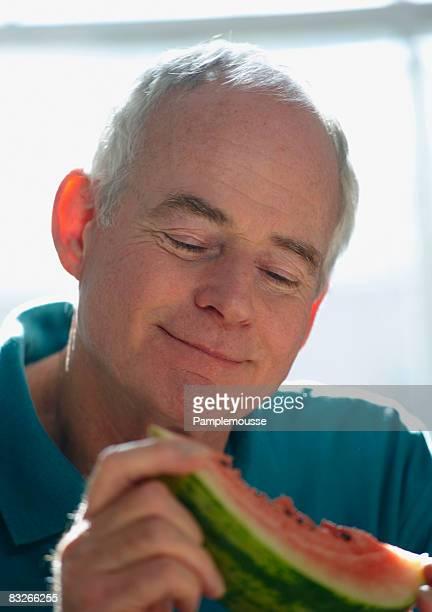 Senior man eating watermelon