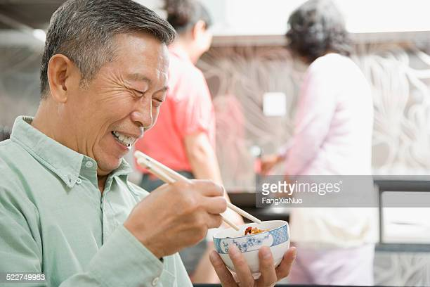 Senior man eating with chopsticks, women in background
