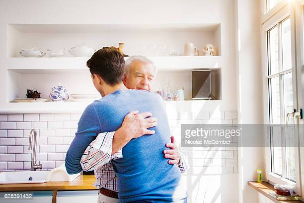 senior man embraces mature son in sunny kitchen - sohn stock-fotos und bilder
