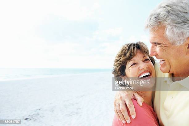 Senior man embracing a smiling woman on beach