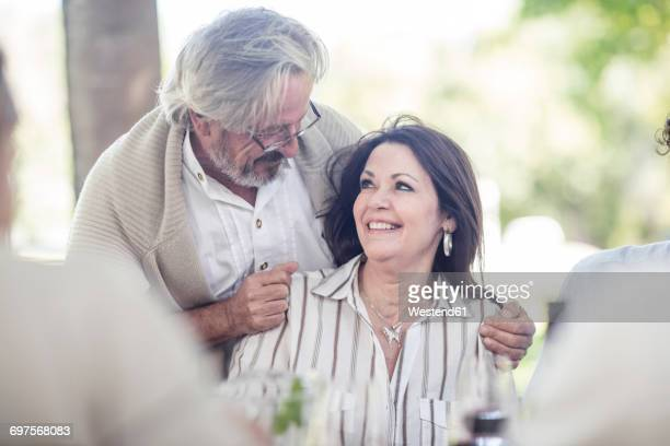 Senior man embracing his wife at outdoor table