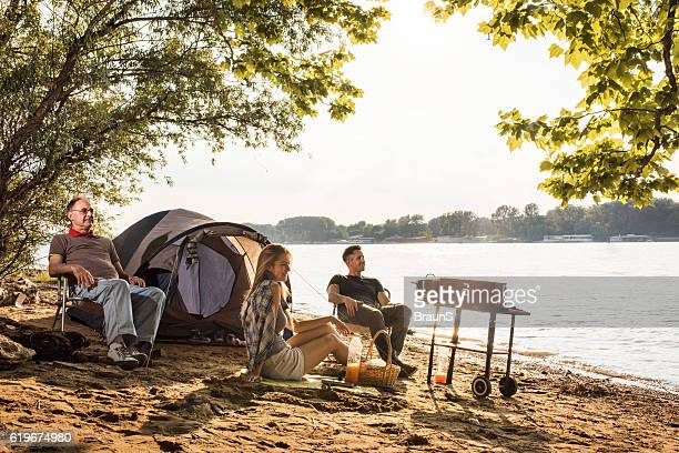 Senior man enjoying on a camping with his adult children.