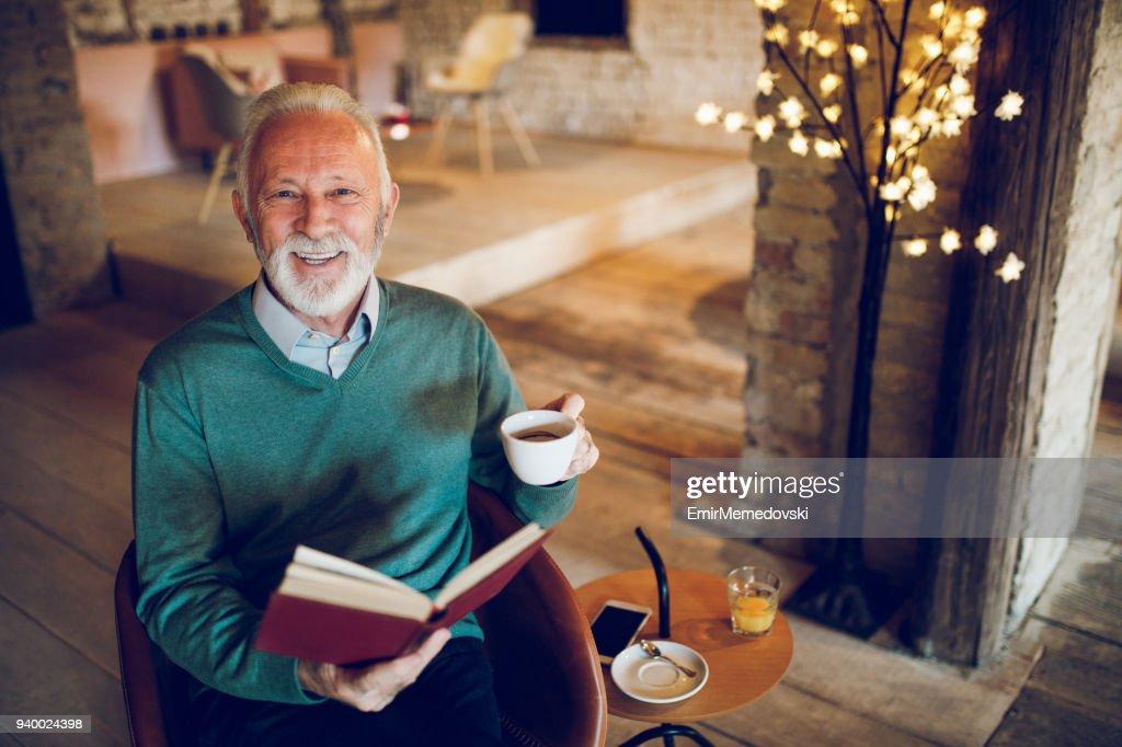 Senior man enjoying reading a book indoors : Stock Photo