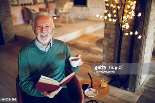 Senior man enjoying reading a book indoors