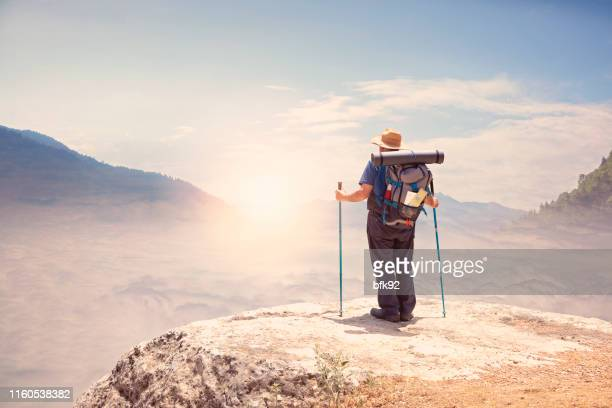 senior man enjoying the view of mountains and clouds on top of mountains at sunrise or sunset. - trabzon stock photos and pictures