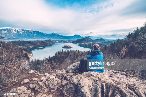 senior man njuter av utsikten över sjön bled i slovenien, europa - bledsjön bildbanksfoton och bilder
