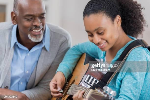 Senior man enjoys watching granddaughter play guitar