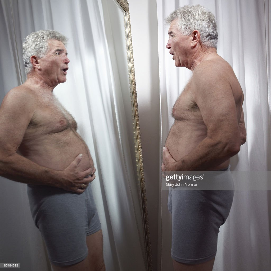 Senior man examines stomach in mirror : ストックフォト